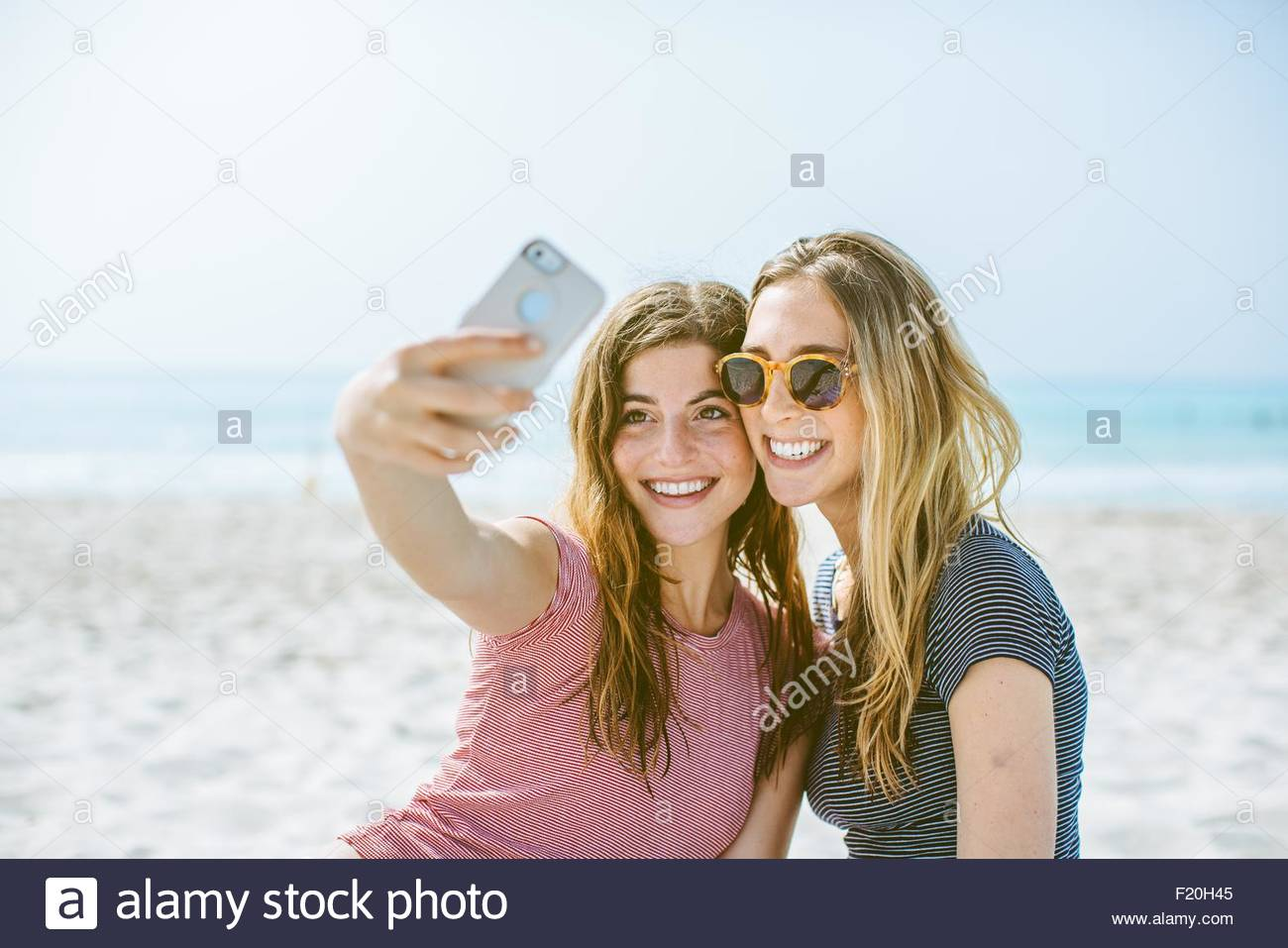 Two young female friends taking smartphone selfie on beach - Stock Image