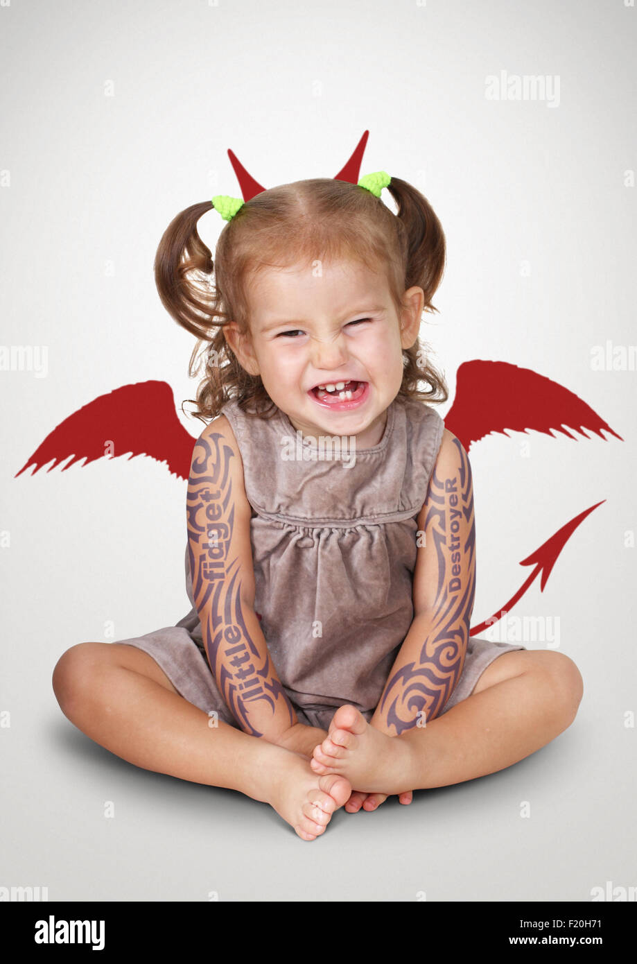 Portrait of bad child with tatoo and devil horns, disobedient baby concept - Stock Image