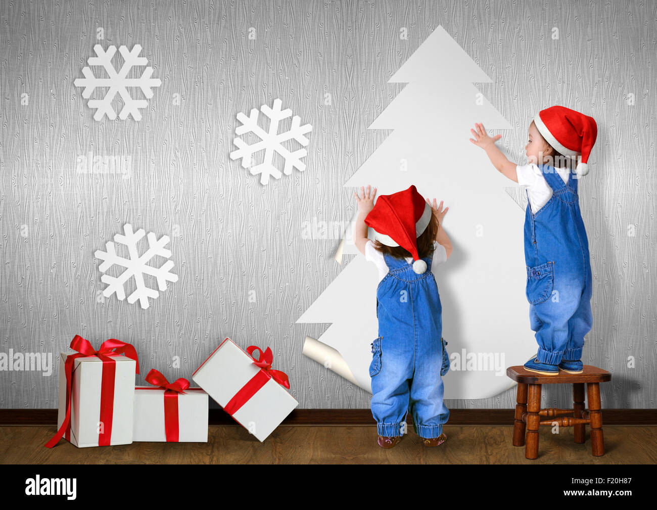 Little twins dressed Santa hat, glue Christmas tree on wall at home, xmas concept - Stock Image