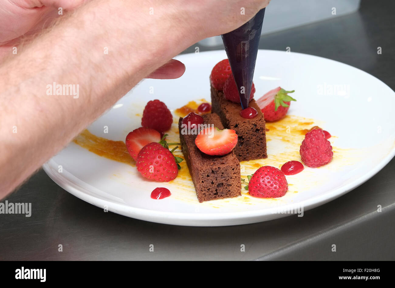chef putting finishing touches to sweet dessert - Stock Image