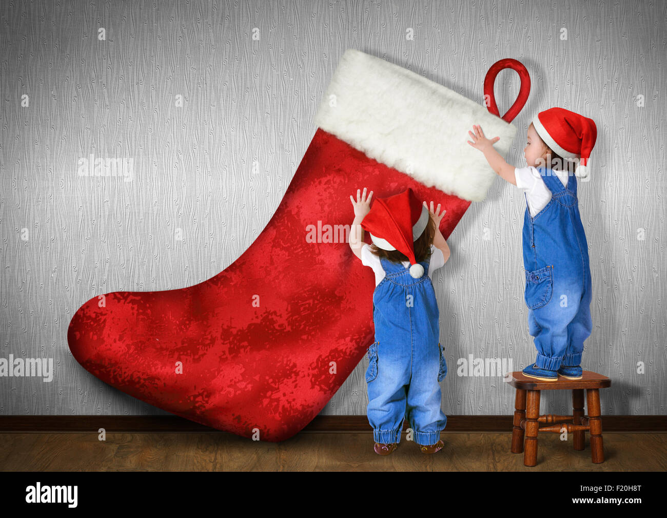 Little twins dressed Santa hat, hangs big Christmas stocking for gifts, xmas concept - Stock Image