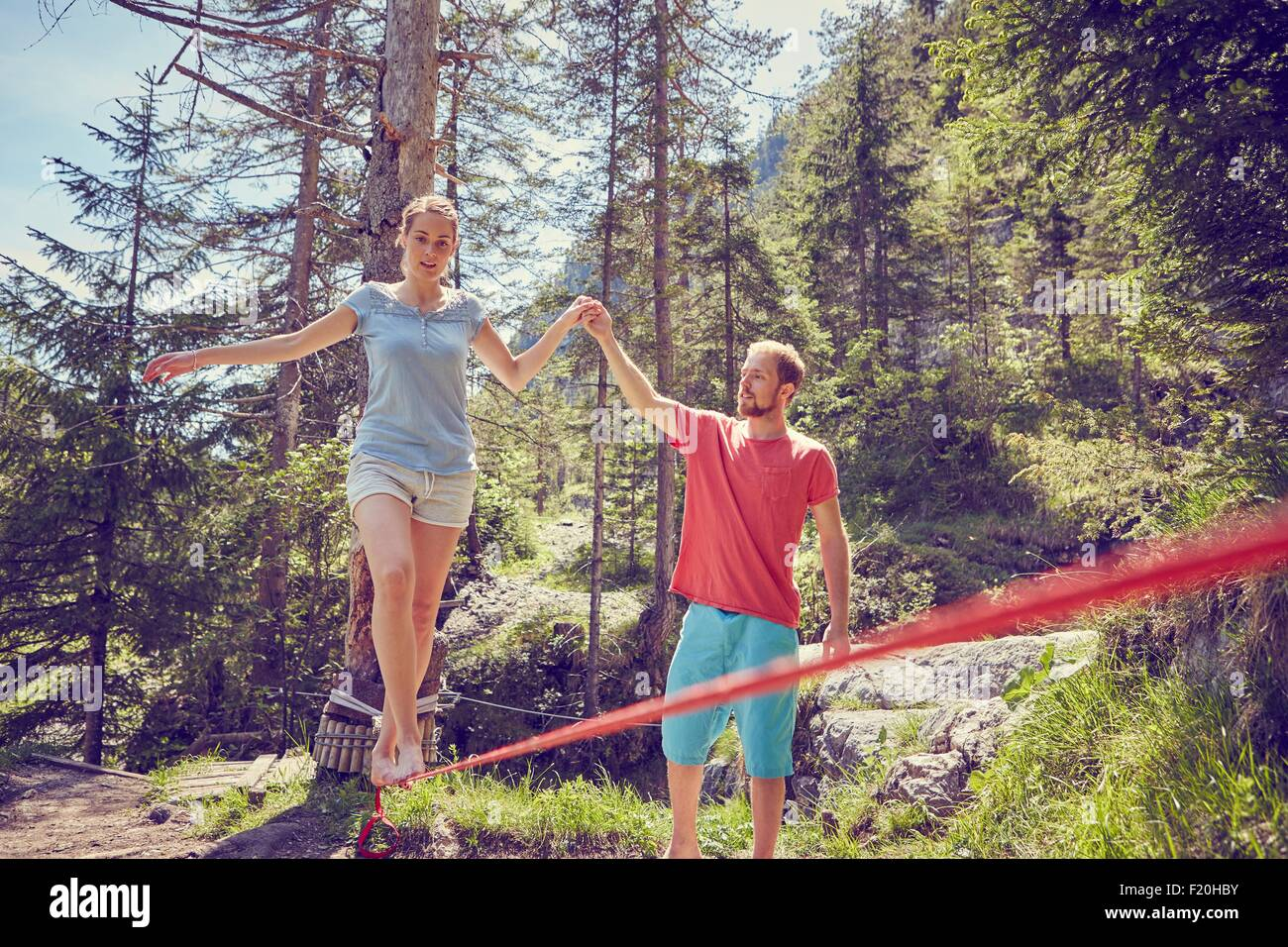 Woman balancing on rope with help from man, Ehrwald, Tyrol, Austria - Stock Image