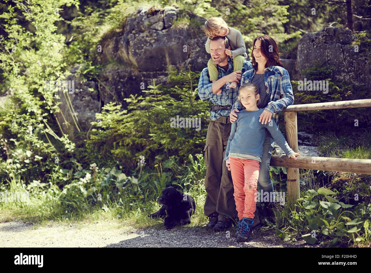 Portrait of family, in forest, standing by fence - Stock Image