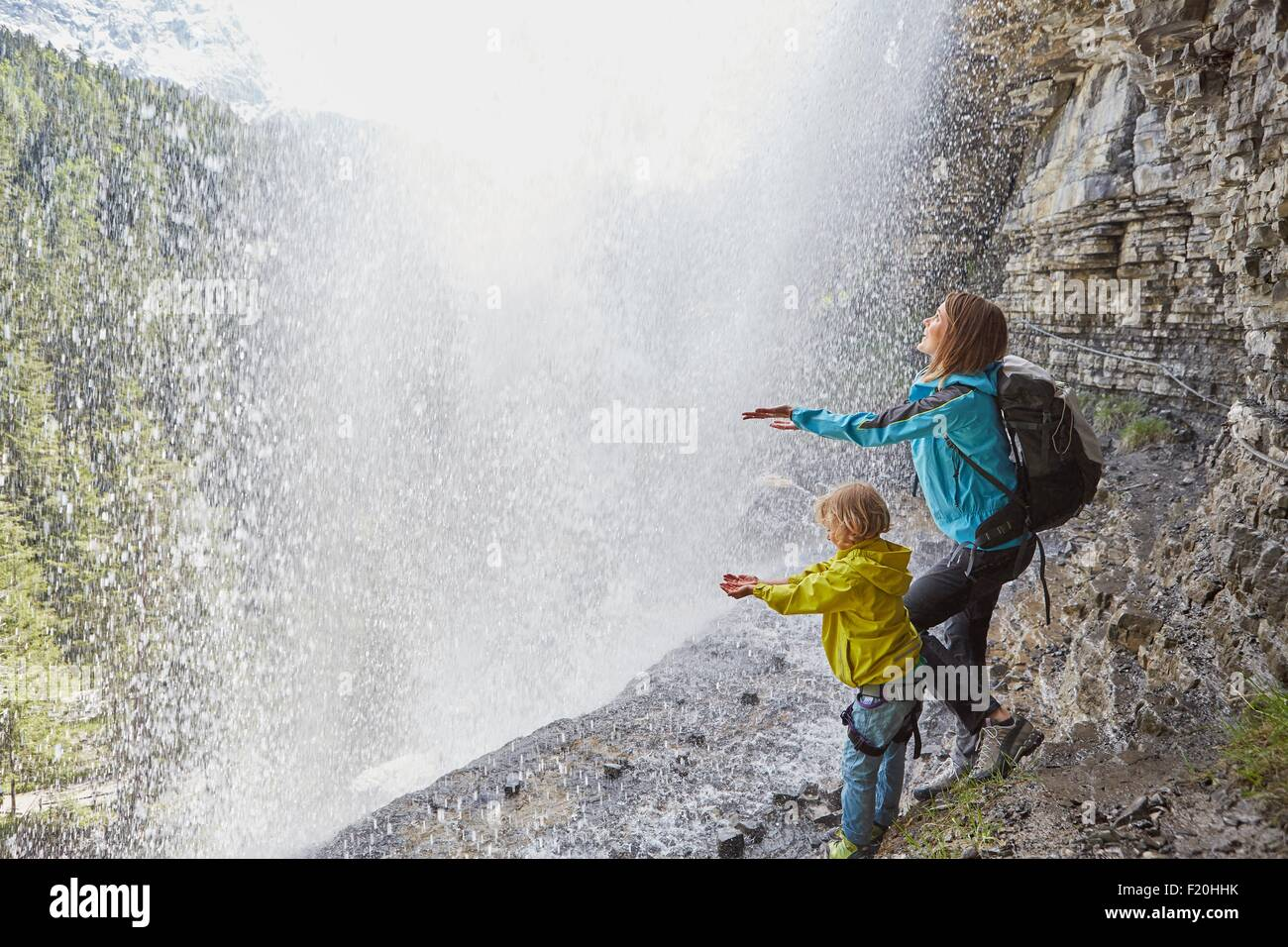 Mother and son, standing underneath waterfall, hands out to feel the water, rear view - Stock Image