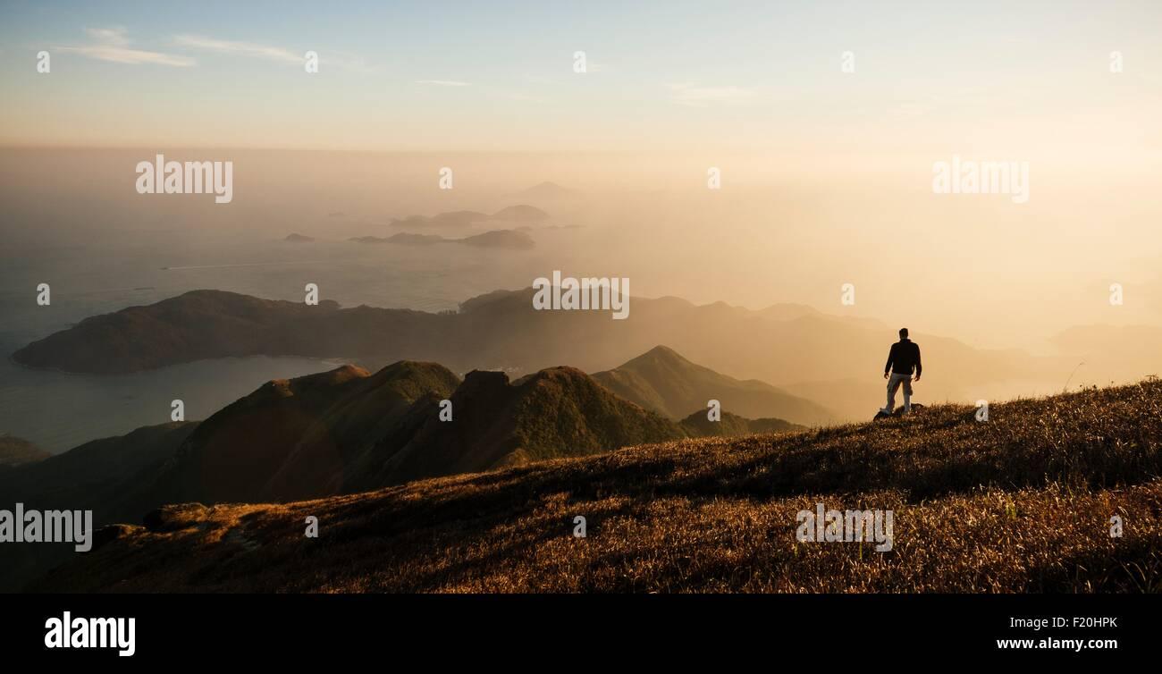 Rear view of hiker hiking on Lantau Peak, Lantau Island, Hong Kong, China - Stock Image