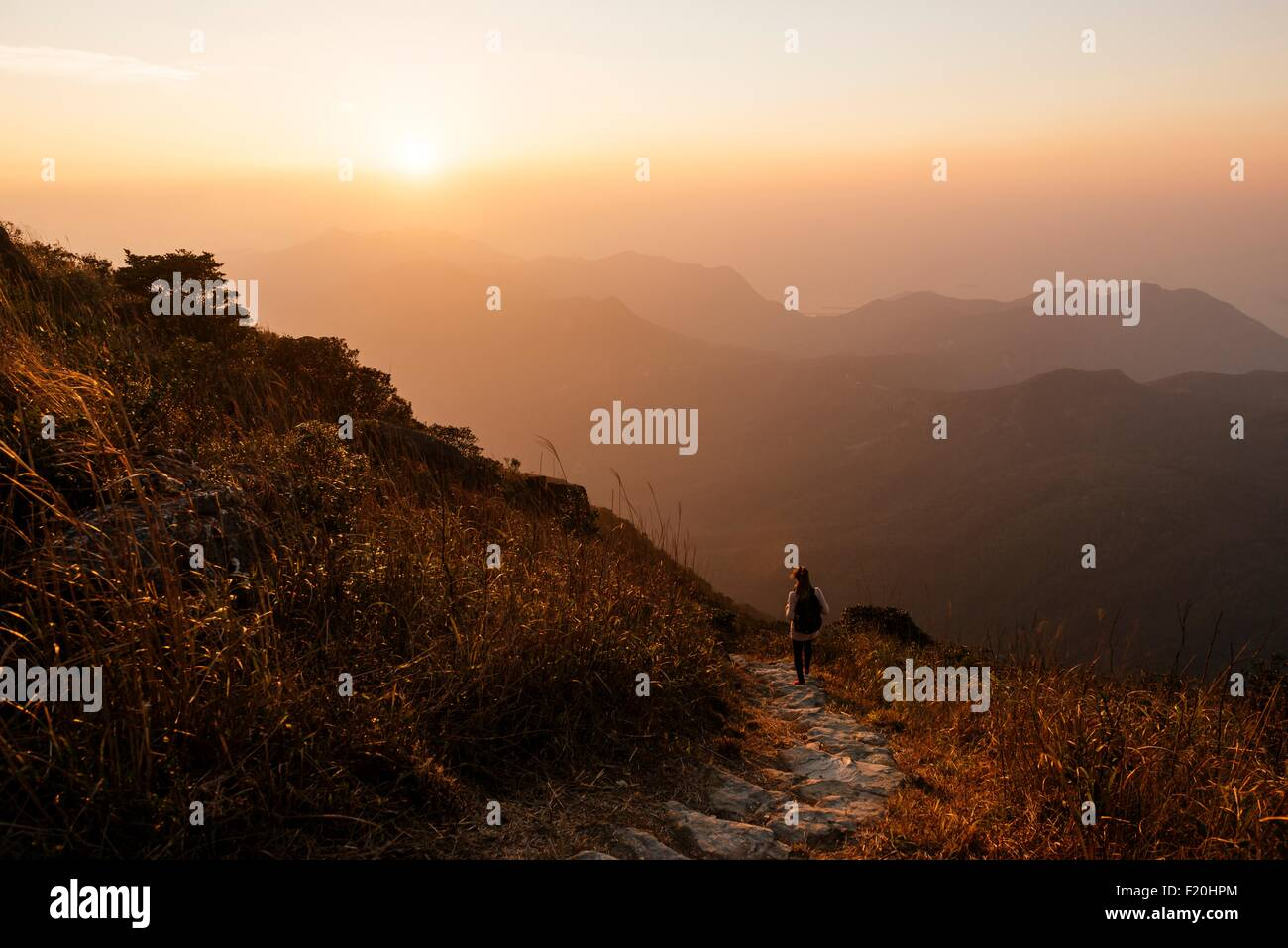 Rear view of hiker hiking along trail on Lantau Peak, Lantau Island, Hong Kong, China - Stock Image