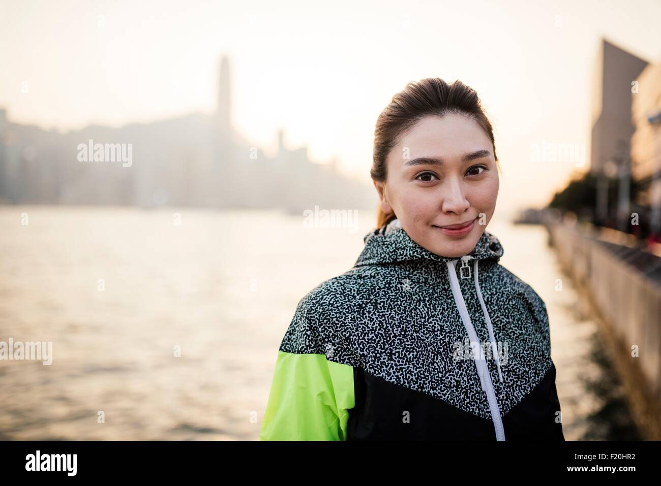 Portrait of young woman wearing tracksuit top in front of water smiling - Stock Image