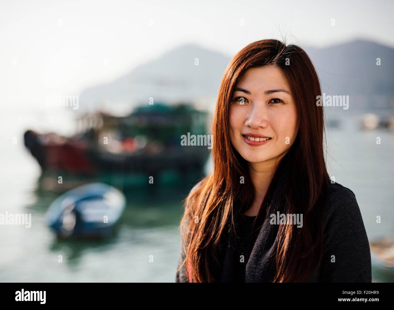 Portrait of mid adult woman in front of boats on water, looking at camera smiling - Stock Image
