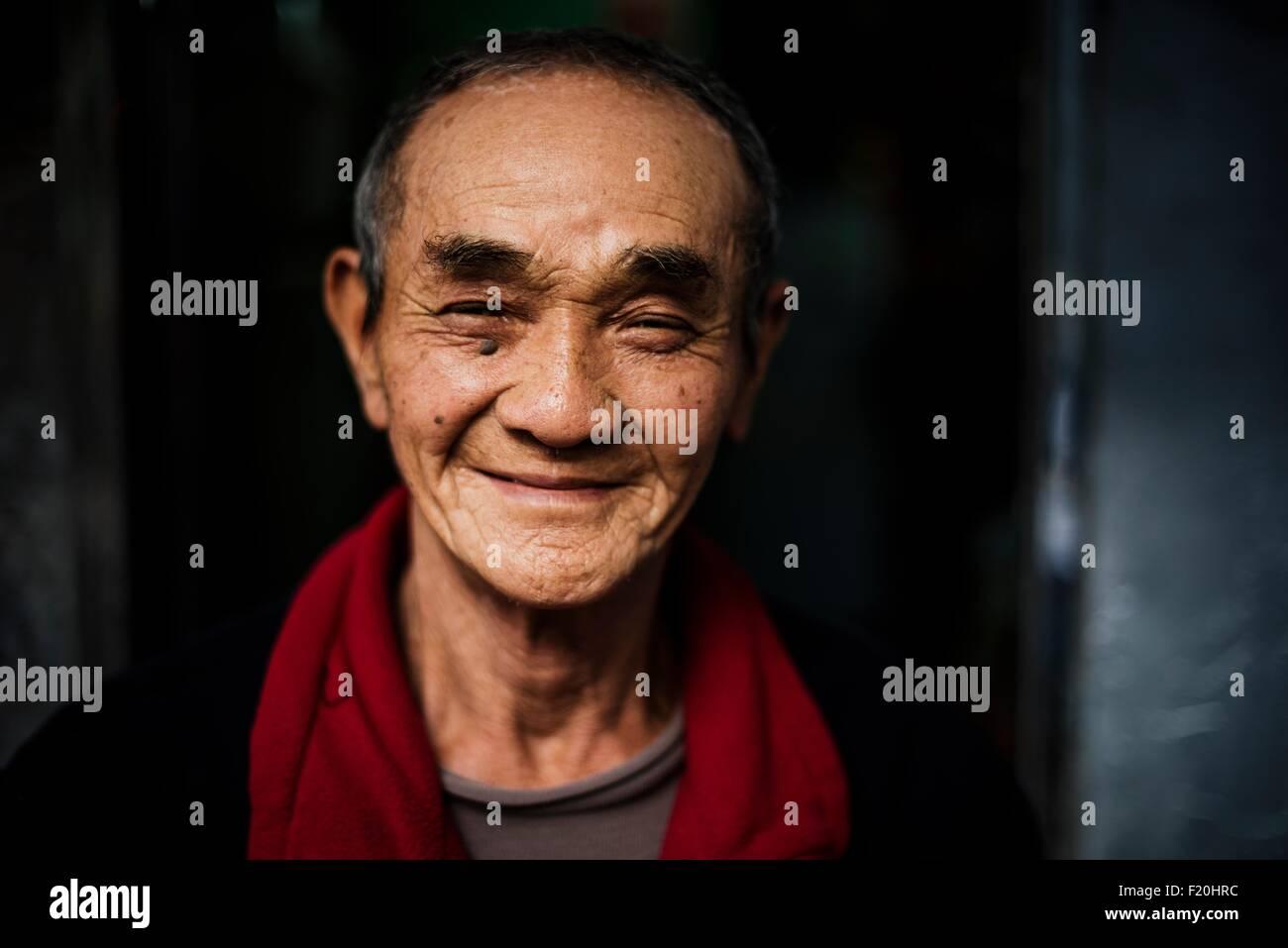 Portrait of senior man wearing red scarf around neck looking at camera smiling - Stock Image