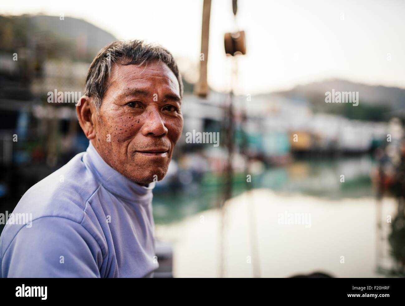 Portrait of senior man, side view, in front of boats on water, looking at camera - Stock Image