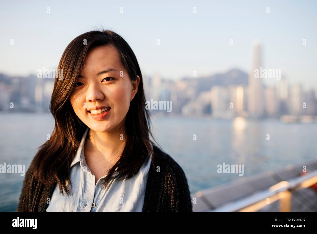 Portrait of young woman with long hair wearing shirt and cardigan in front of water, looking at camera - Stock Image