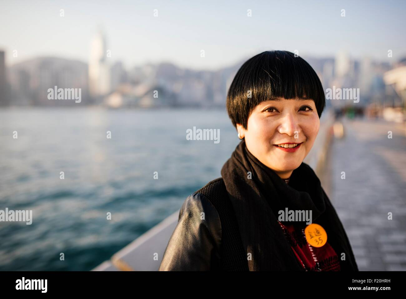 Portrait of mid adult woman with short hair in front of water looking at camera smiling - Stock Image