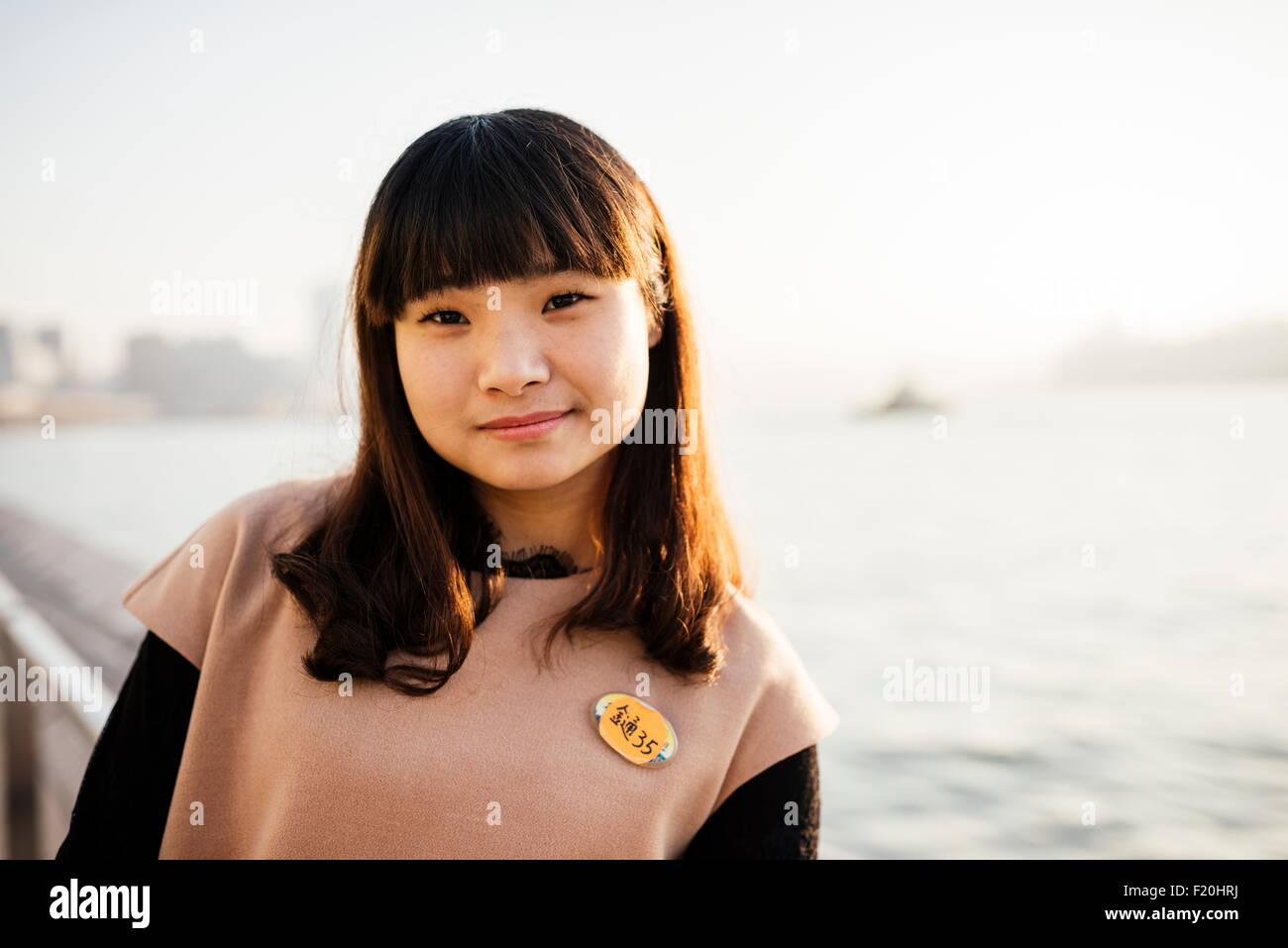 Portrait of young woman with fringe in front of water, looking at camera - Stock Image