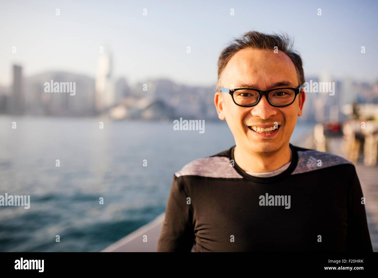 Portrait of mid adult man wearing glasses in front of water, looking at camera smiling - Stock Image