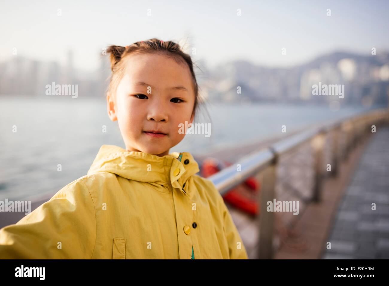 Portrait of young girl wearing yellow coat in front of water looking at camera - Stock Image