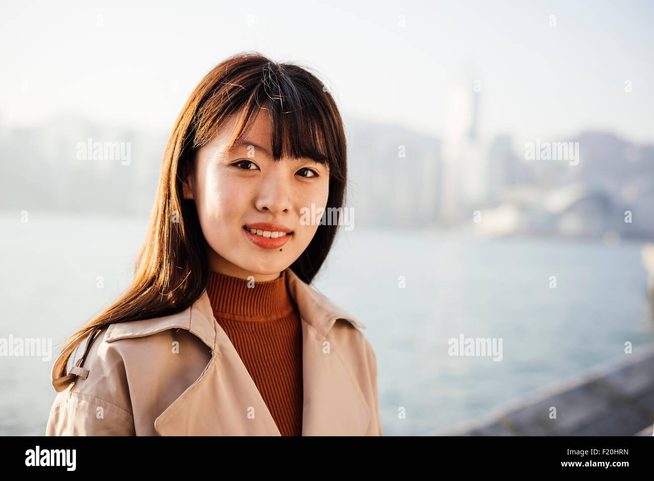 Portrait of young woman with long hair in front of water looking at camera smiling - Stock Image