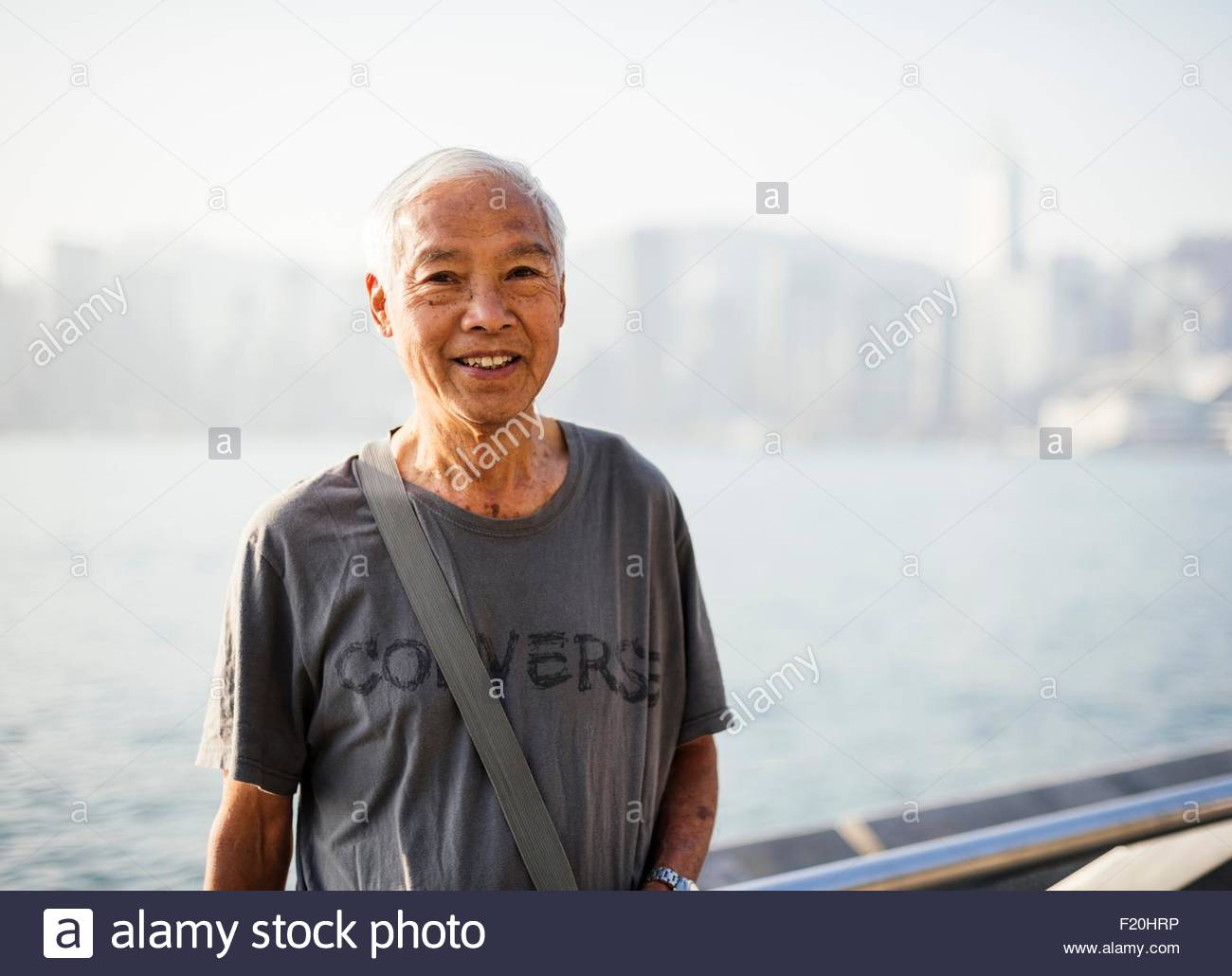 Portrait of grey haired senior man wearing tshirt looking at camera smiling - Stock Image