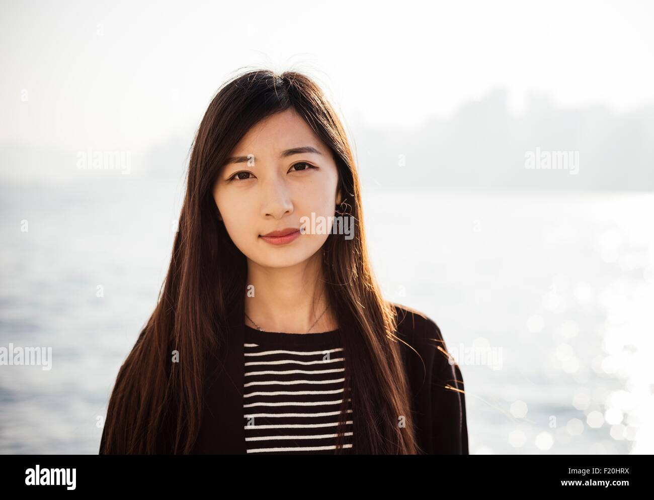 Portrait of young woman with long brunette hair wearing striped top looking at camera - Stock Image