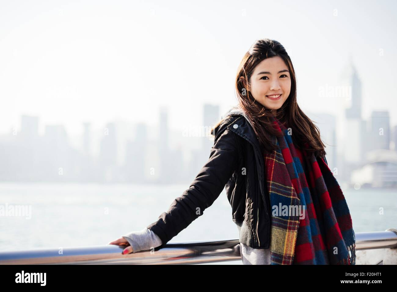 ce81be197 Portrait of young woman wearing checked scarf and leather jacket, looking  at camera - Stock