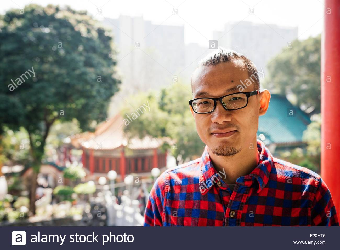 Portrait of young man wearing glasses and checked shirt in front of traditional pagoda, looking at camera - Stock Image