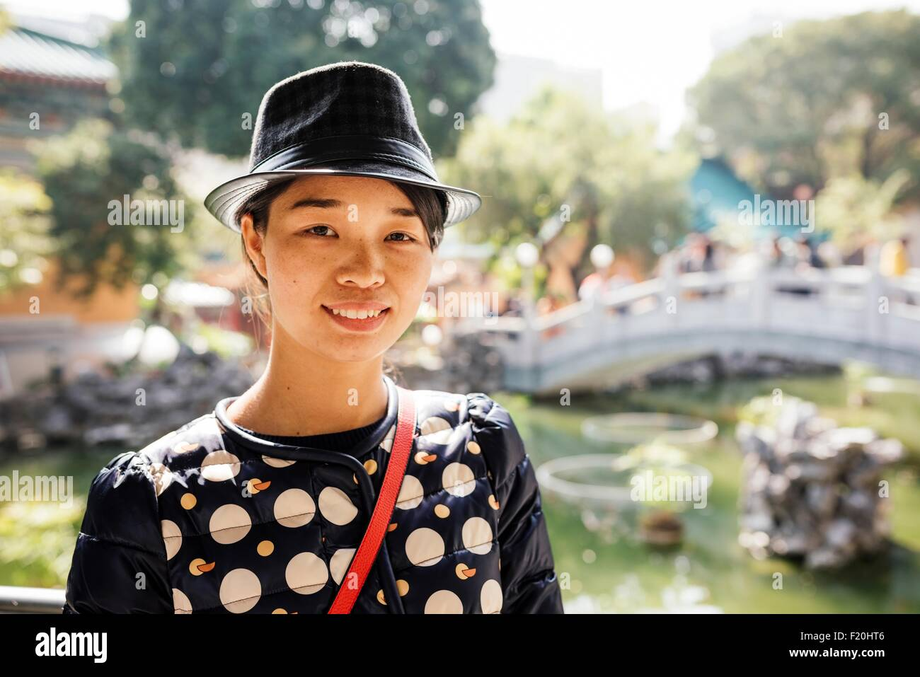 Portrait of young woman wearing hat in front of chinese garden bridge, looking at camera - Stock Image