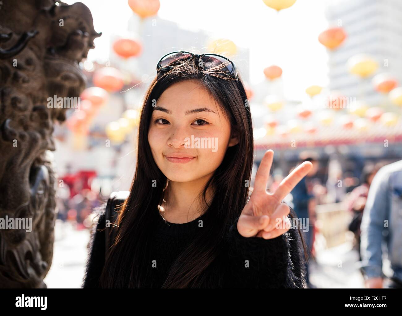Portrait of young woman with long hair and sunglasses on head doing peace sign, looking at camera - Stock Image