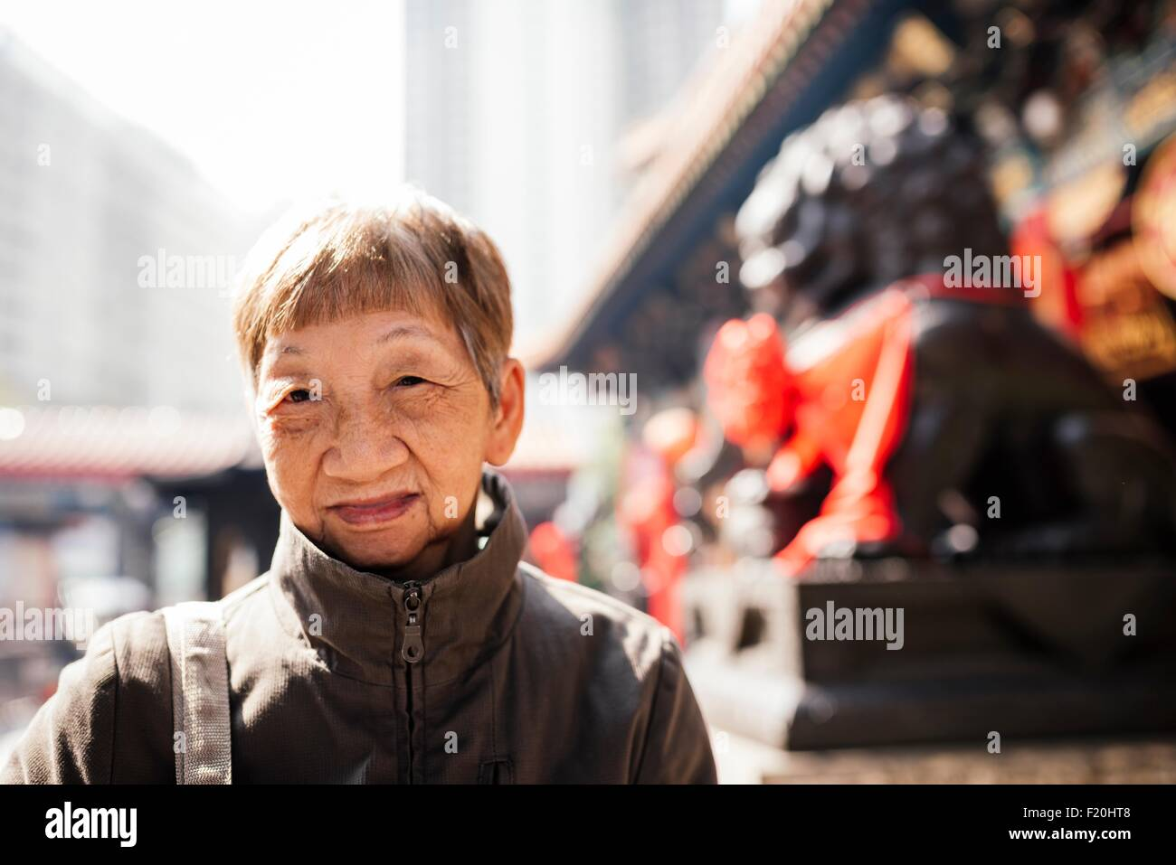 Portrait of senior woman wearing coat in front of lion statue, looking at camera - Stock Image