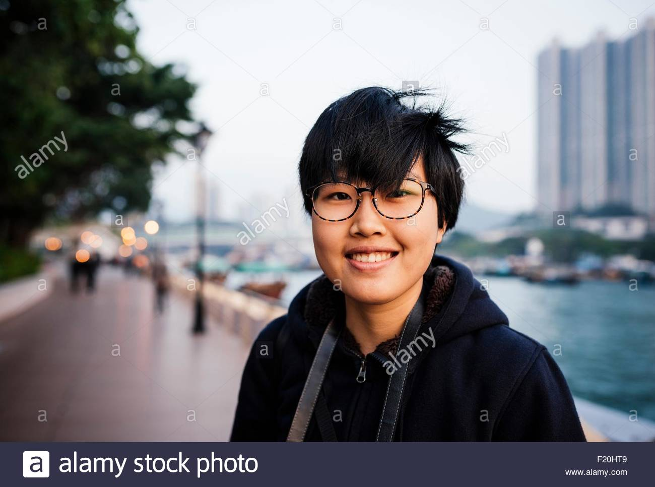 Portrait of mid adult woman with short hair wearing glasses, in front of water, looking at camera - Stock Image