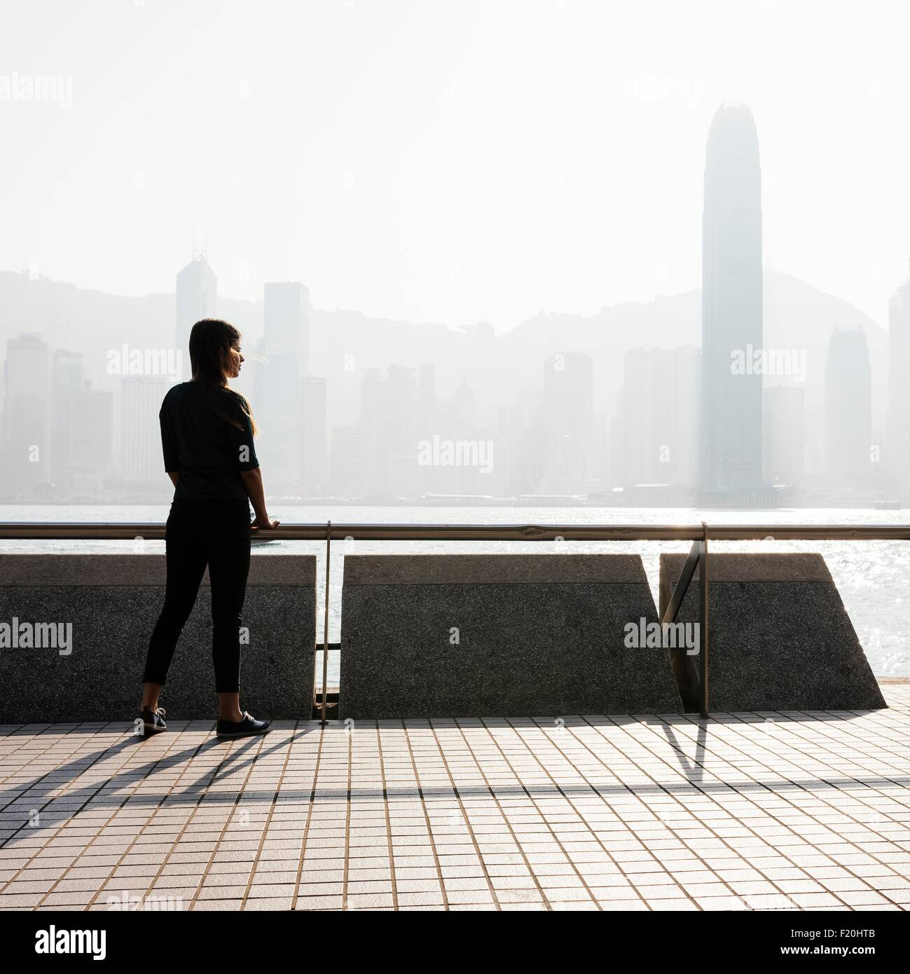 Silhouetted side view of young woman standing looking out over water at skyline, Hong Kong, China - Stock Image