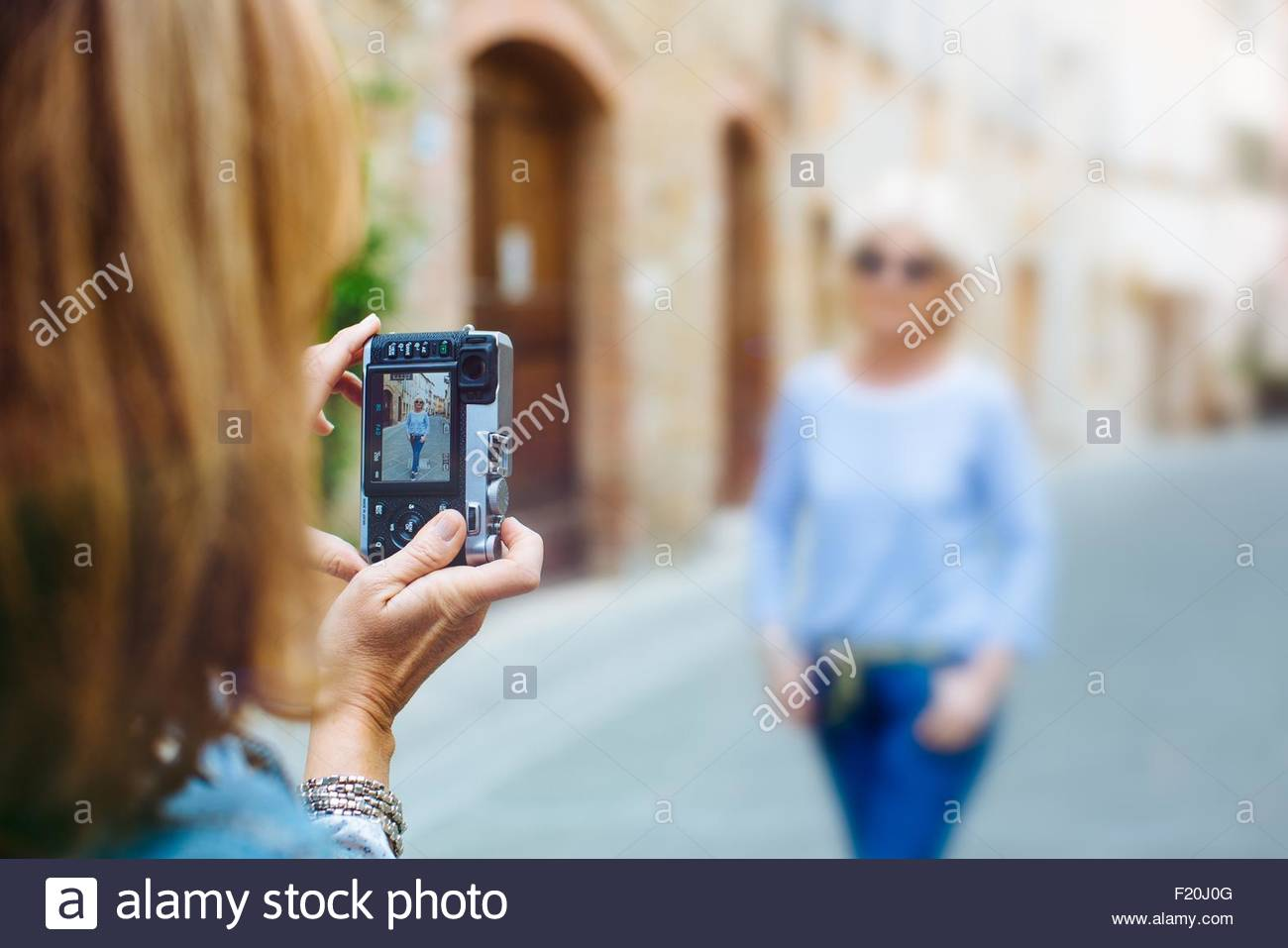 Mature woman photographing best friend on street - Stock Image