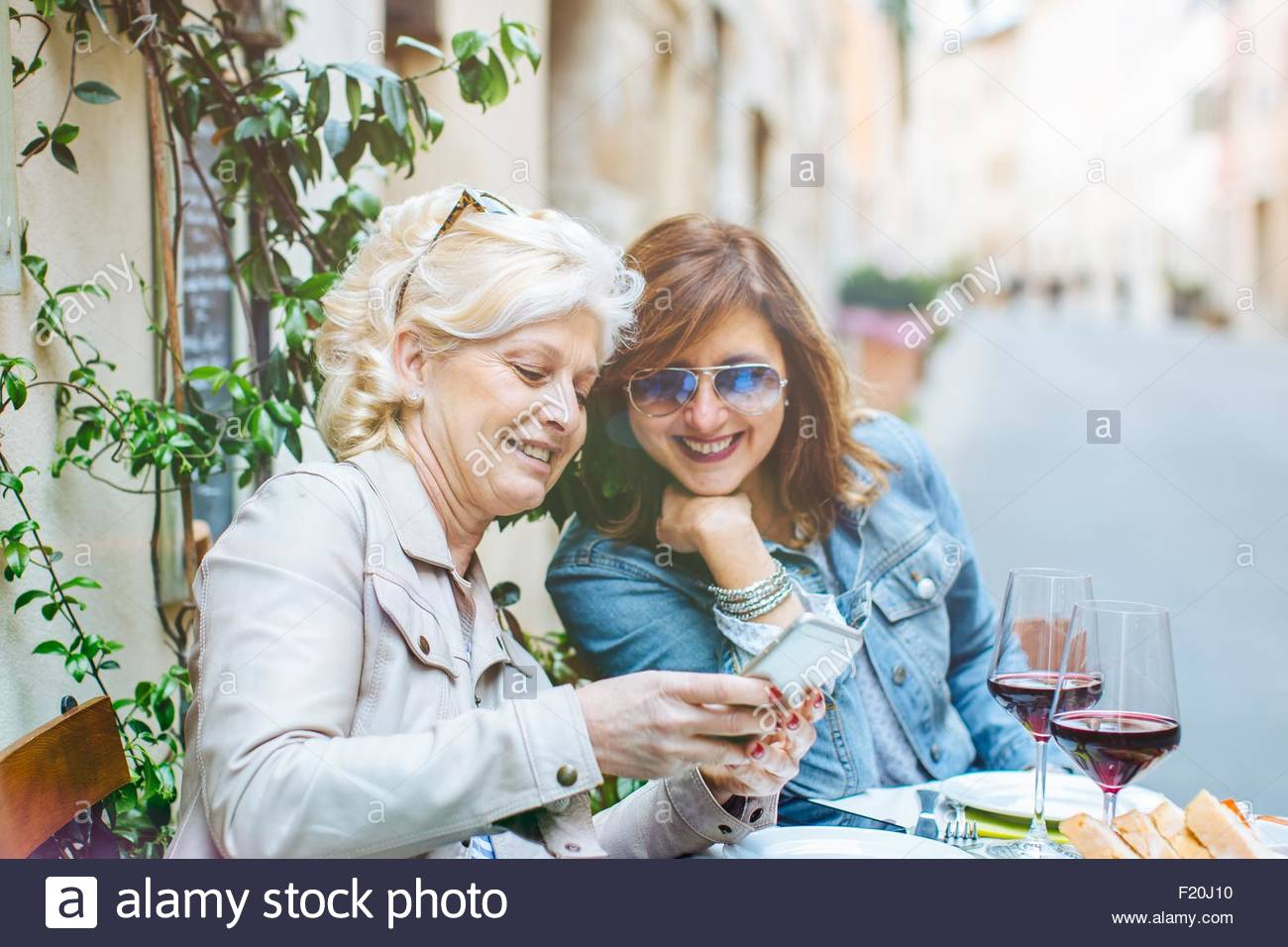 Two mature female friends looking at smartphone at sidewalk cafe, Tuscany, Italy - Stock Image