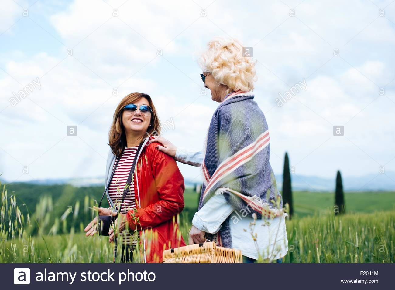 Two mature women with picnic basket in wheatfield, Tuscany, Italy - Stock Image