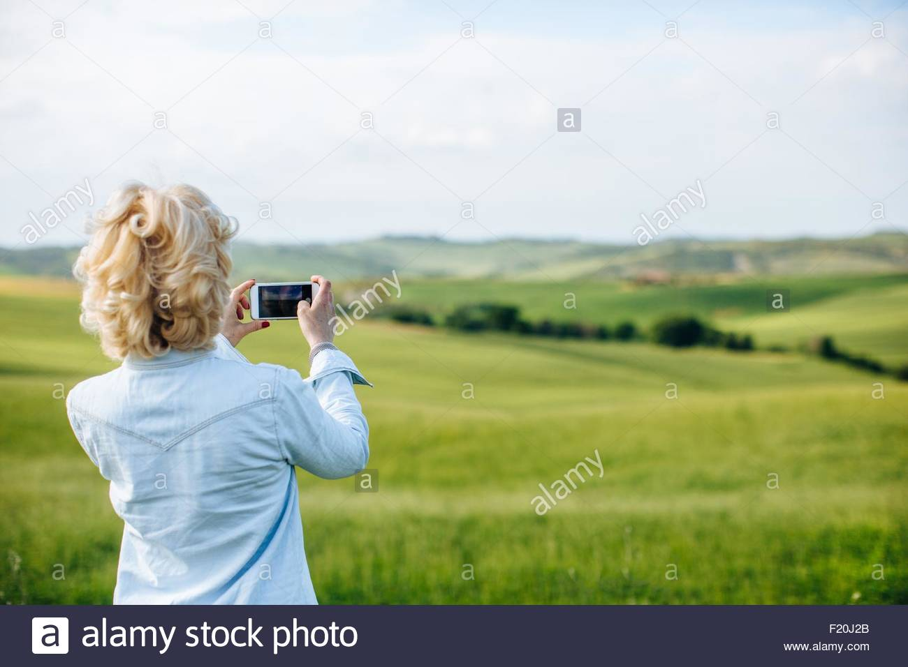 Rear view of mature woman photographing landscape, Tuscany, Italy - Stock Image
