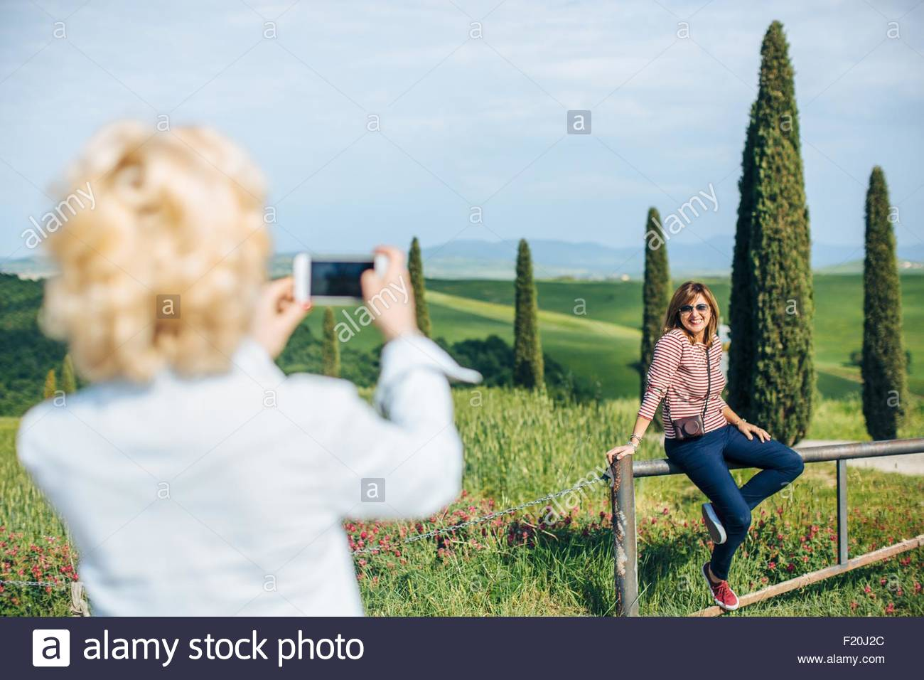 Two mature female friends taking smartphone photograph in landscape, Tuscany, Italy Stock Photo