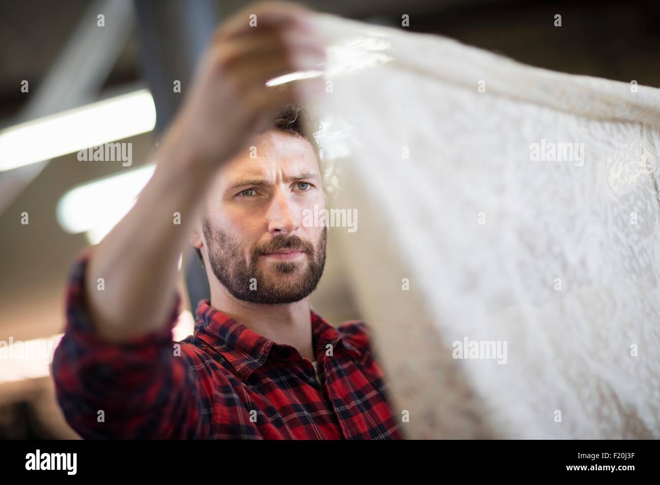 Male weaver checking lace textile in old textile mill - Stock Image