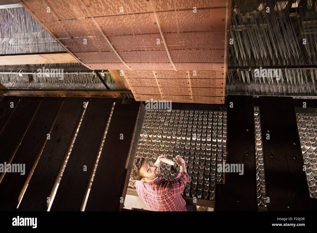 Overhead view of male weaver using old weaving machine in textile mill - Stock Image