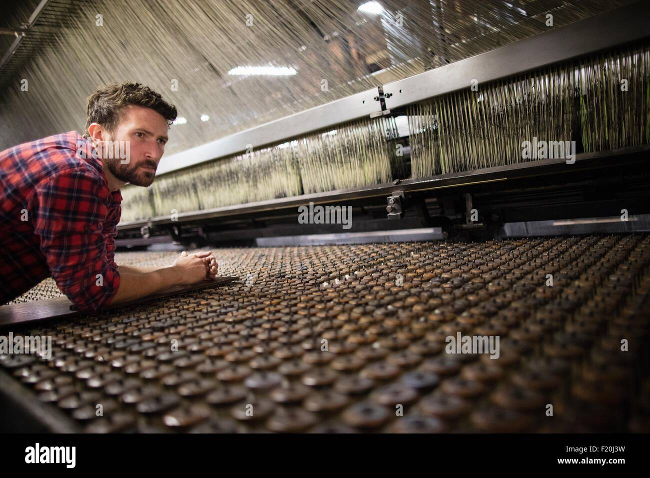 Male weaver monitoring old weaving machine in textile mill - Stock Image