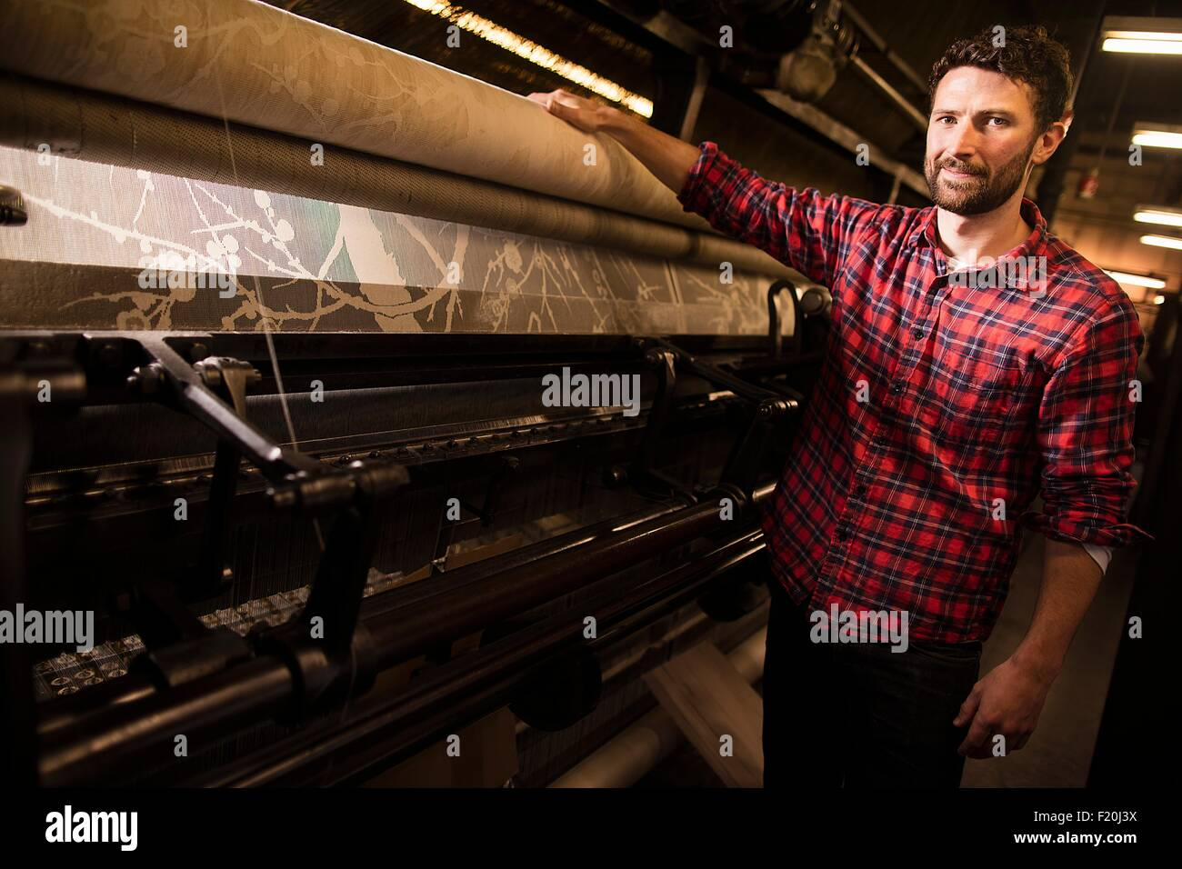Portrait of male weaver next to old weaving machine in textile mill - Stock Image