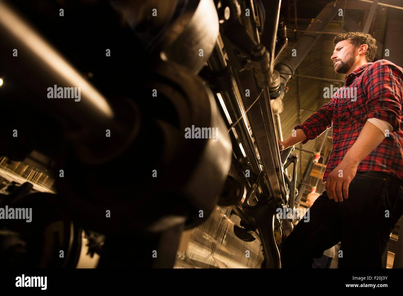 Low angle view of male weaver using old weaving machine in textile mill - Stock Image