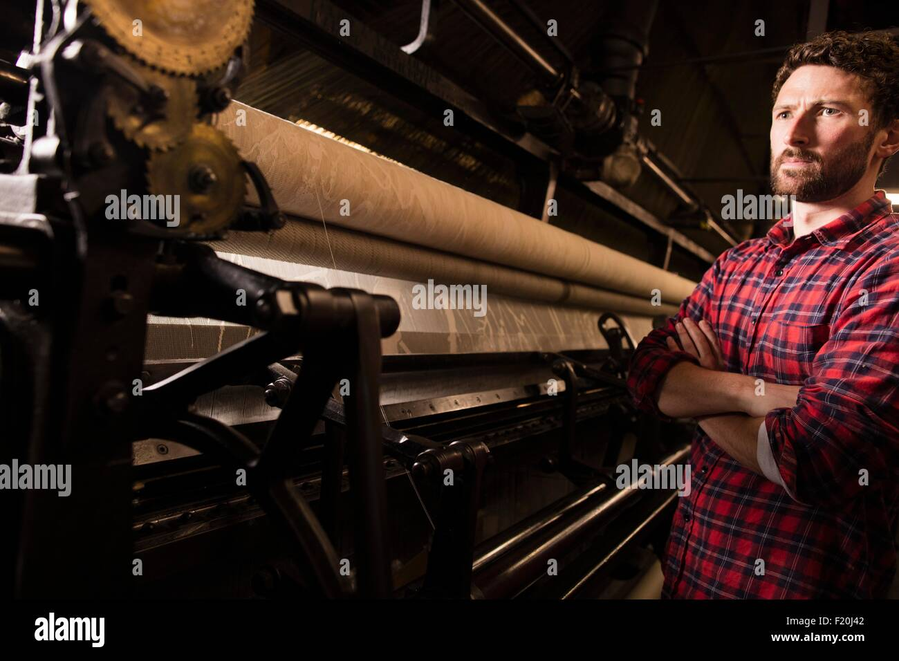 Portrait of young male weaver and old weaving machine in textile mill - Stock Image