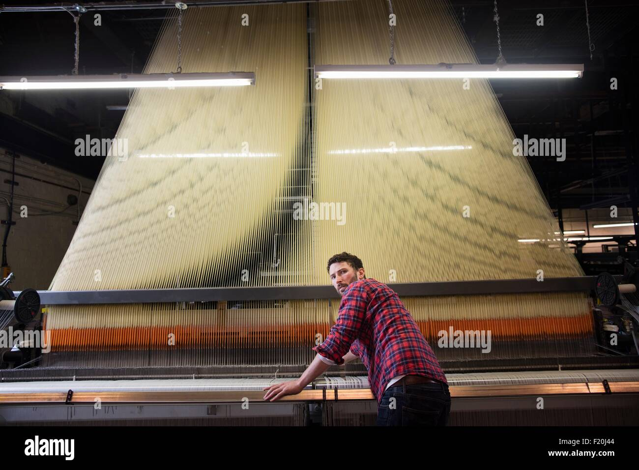 Overhead portrait of young male weaver at old weaving machine in textile mill Stock Photo