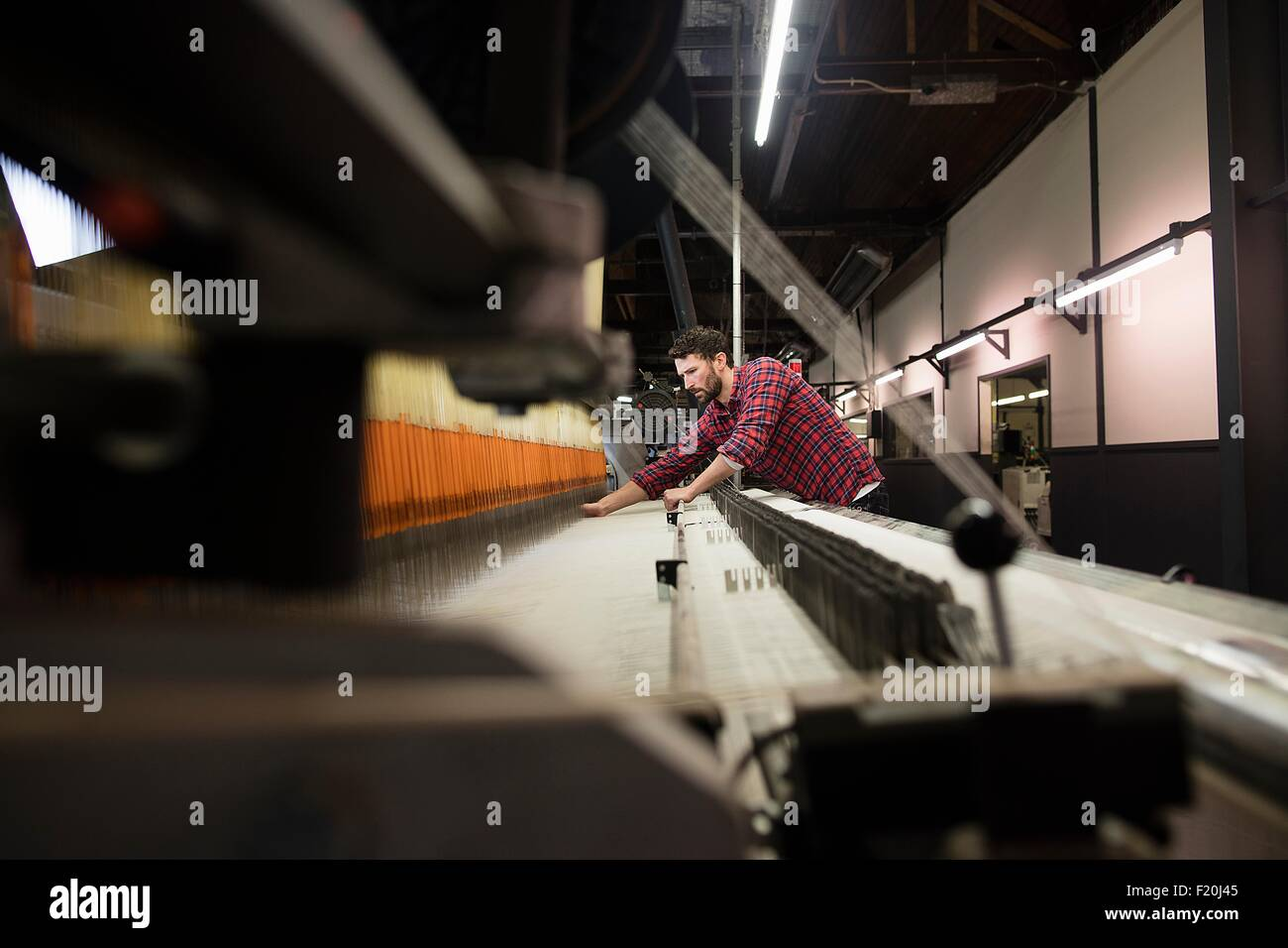 Young male weaver working at old weaving machine in textile mill - Stock Image