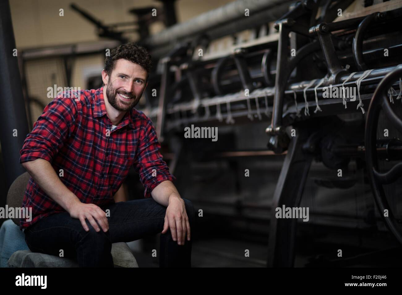 Portrait of young male weaver at old weaving machine in textile mill - Stock Image