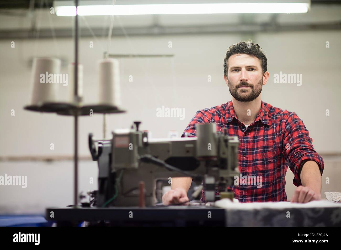 Portrait of male textile designer using sewing machine in old textile mill - Stock Image