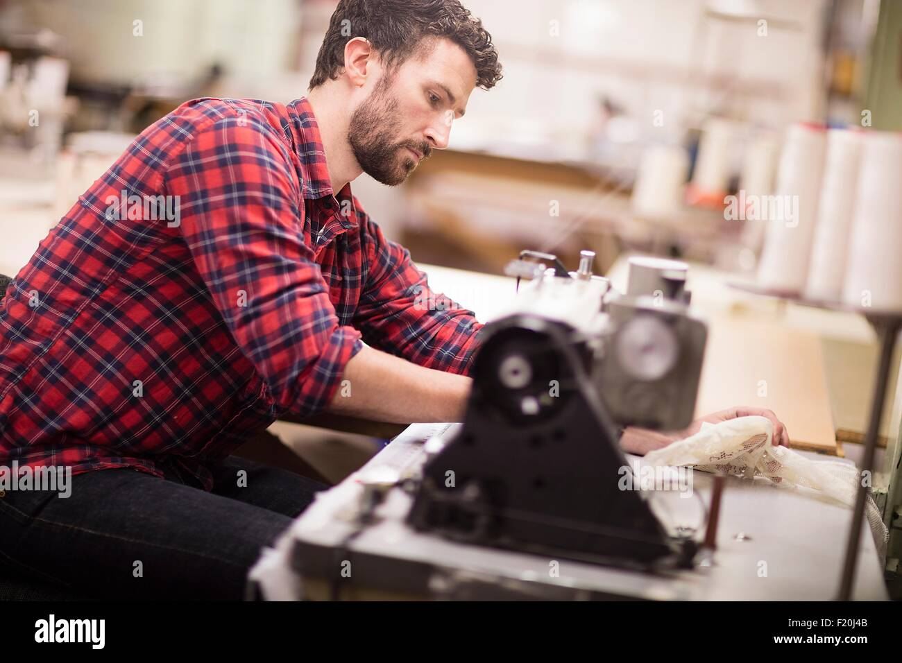 Male weaver using sewing machine in old textile mill - Stock Image