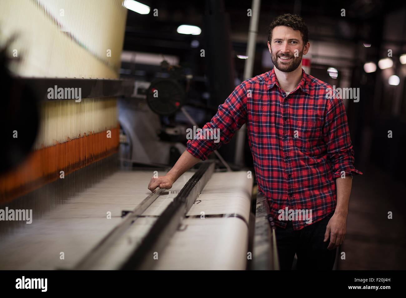 Portrait of young male weaver using old weaving machine in textile mill - Stock Image