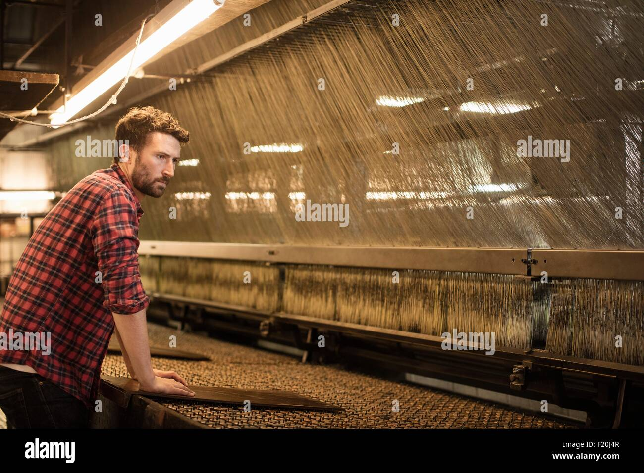 Male lace weaver using old weaving machine in textile mill - Stock Image