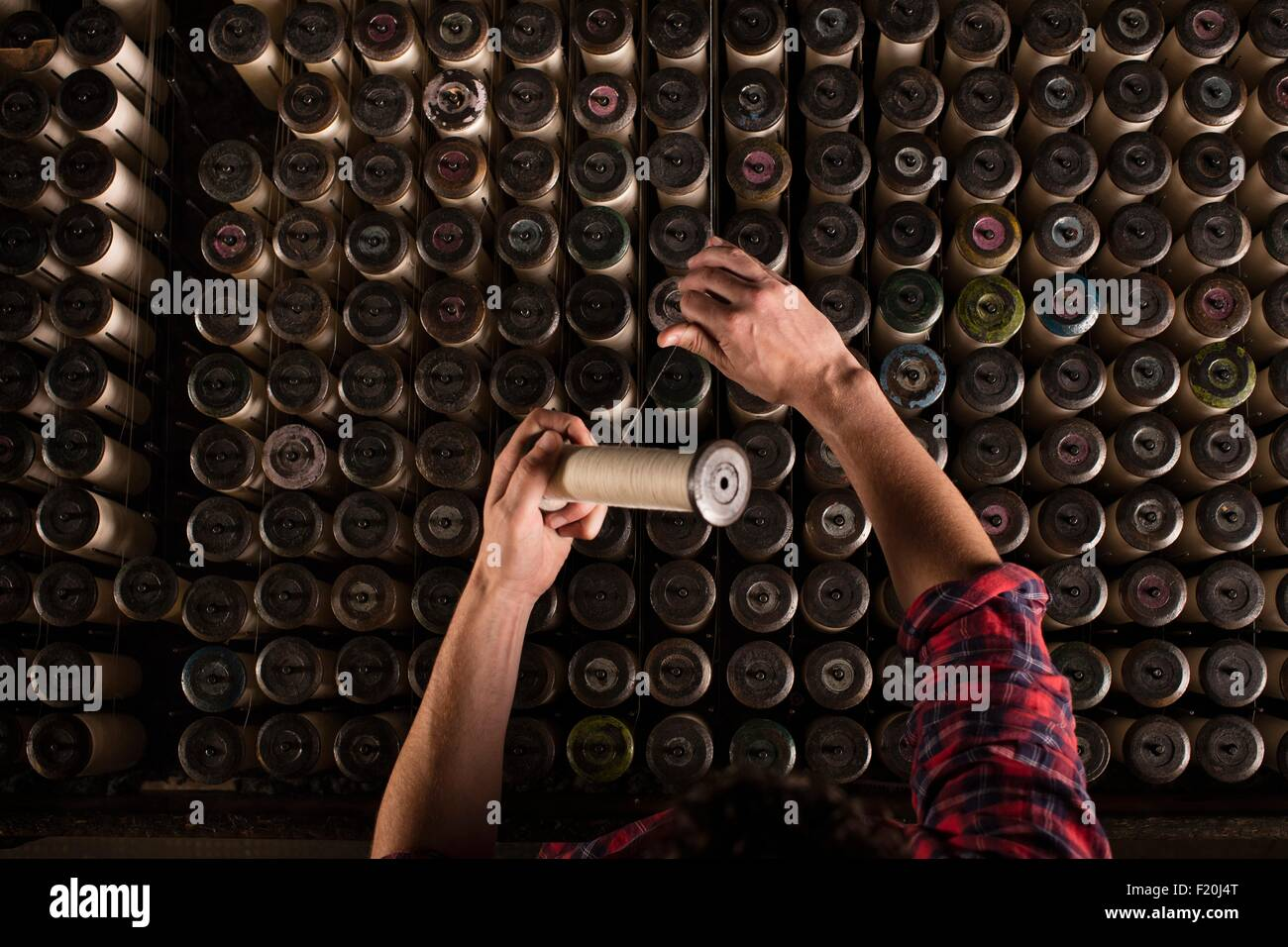Hands of male lace weaver replacing threads on old weaving machine in textile mill - Stock Image