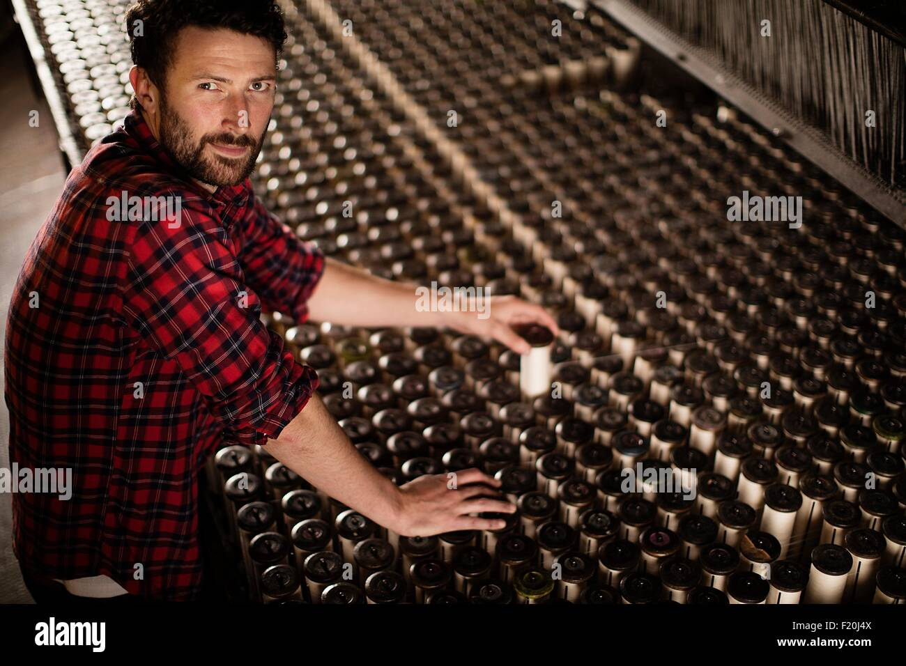 Portrait of male lace weaver replacing bobbin on old weaving machine in textile mill - Stock Image