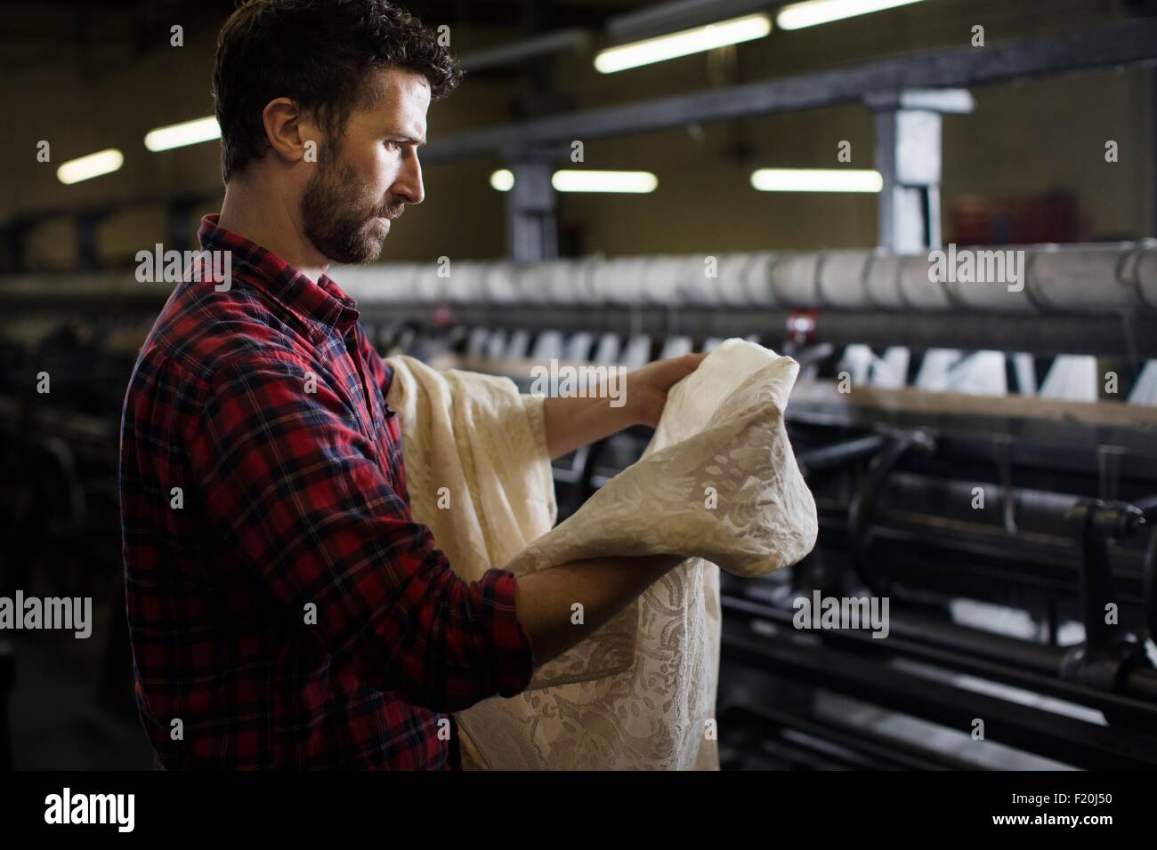 Portrait of male weaver examining lace from old weaving machine in textile mill - Stock Image